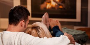 man and woman cuddling in front of a fire
