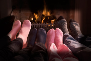 four pairs of feet in front of a fire